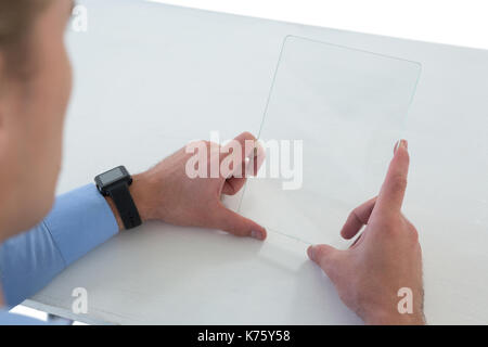 High angle view of businessman using glass interface at table against white background - Stock Photo