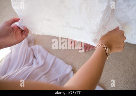 High angle cropped hands of bridesmaid adjusting bride dress in fitting room - Stock Photo