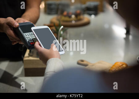 Woman paying bill through smartphone using NFC technology in restaurant - Stock Photo