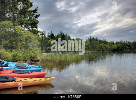 a group of four, brightly coloured kayaks wait on the lake or shore in the early morning - Stock Photo