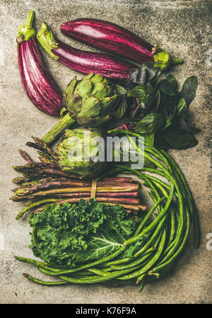 Flat-lay of fresh green and purple vegetables - Stock Photo