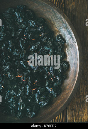 Black dried raisins in vintage plate over rustic wooden background - Stock Photo