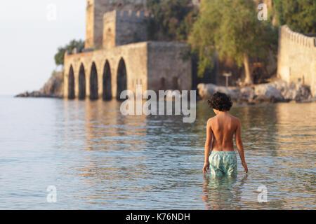Backview of portrait of boy with dark hair wearing swimwear standing in water near Alanya medieval shipyard in mediterrarian - Stock Photo