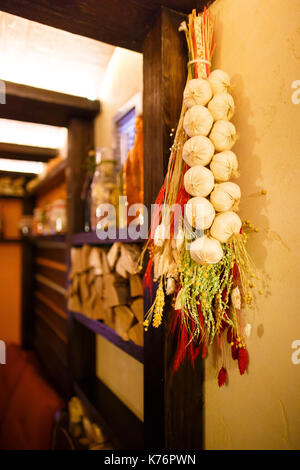 The close-up photo of the artificial onions and grass hanging on the wooden beam in the lovely cafe. - Stock Photo