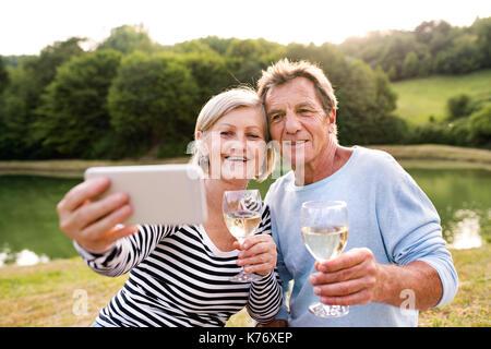Senior couple at the lake having a picnic taking selfie - Stock Photo