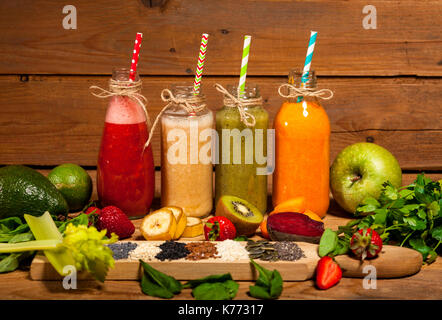 Assortment of fruit and vegetable smoothies in glass bottles with straws on wooden background. - Stock Photo