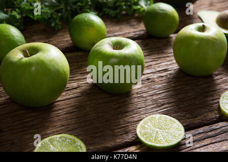 Close-up of green apple and sliced lemon arranged on wooden table - Stock Photo