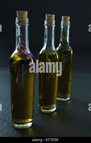 Bottles of olive oil with herbs on black background - Stock Photo