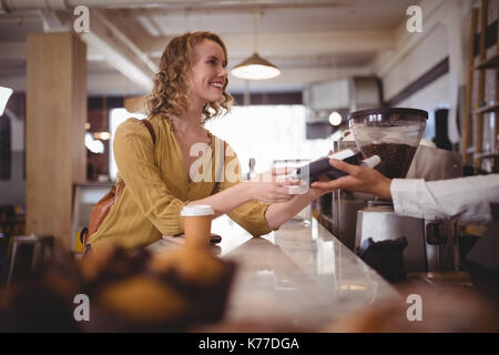 Smiling beautiful female customer paying through card at counter in coffee shop - Stock Photo
