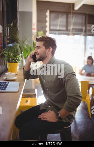 Side view of smiling young man talking on cellphone while sitting at counter in coffee shop - Stock Photo