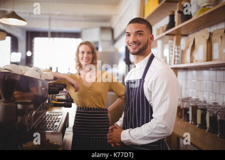 Portrait of smiling young waiter and waitress standing by espresso maker at coffee shop - Stock Photo