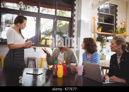 Young man sitting with friends ordering food to waitress at cafe - Stock Photo