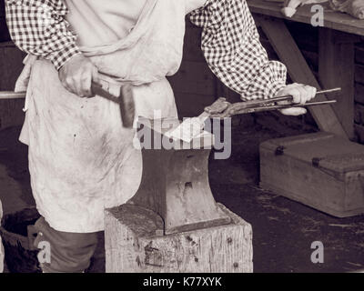 Blacksmith at work in historical reenactment - Stock Photo