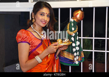 Indian woman standing doing puja on gudi padwa traditional new year for Marathi Hindus - Stock Photo