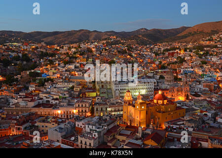 The urban skyline of Guanajuato city at twilight with the Our Lady of Guanajuato Cathedral and the colorful city - Stock Photo