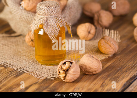 Walnut oil in bottle and nuts on wooden table - Stock Photo