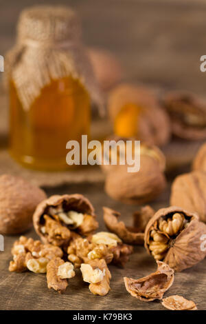 Walnuts and walnuts oil on old wooden table - Stock Photo
