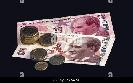 Turkish bank notes and coins on a black background. - Stock Photo