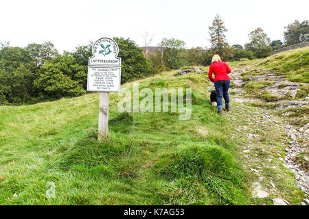 A woman walking with her dog past a National Trust Omega Sign saying Latterbarrow, English Lake District, Cumbria, - Stock Photo