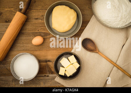 Flatlay collection of tools and ingredients for baking cookies on a dark wooden table. Shot from above - Stock Photo