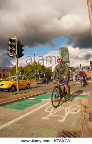 Cycling Manchester Cyclists in cycles lanes amongst the Friday rush hour traffic. Bright & Sunny with heavy clouds - Stock Photo