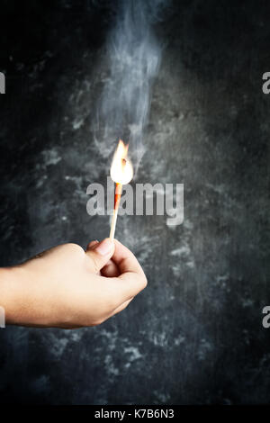 Girl's hand holding a burning match against a dark grunge background. - Stock Photo