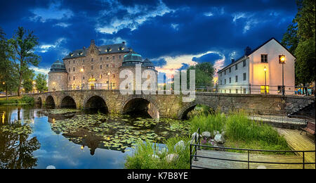 Panoramic HDR image of Orebro Castle and bridge reflecting in water of Svartan river at dusk, Sweden - Stock Photo