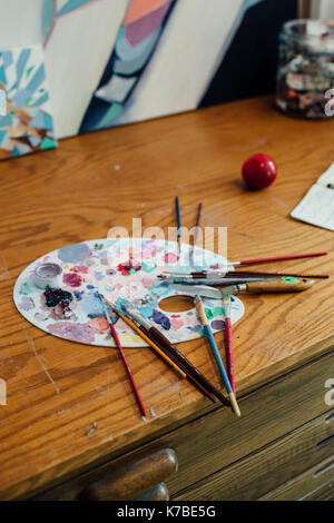 Close-up of paintbrushes with messy colorful palette on wooden table Stock Photo