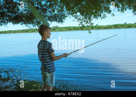 Boy fishing on lake shore - Stock Photo