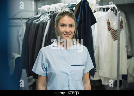 Young woman with clothes racks in foreground, portrait - Stock Photo
