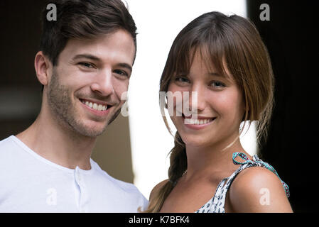 Young couple smiling cheerfully, portrait - Stock Photo