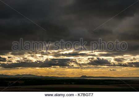 Sunset over East Lothian looking towards Edinburgh, Scotland, UK, with distinctive outlines of Pentland Hills and - Stock Photo