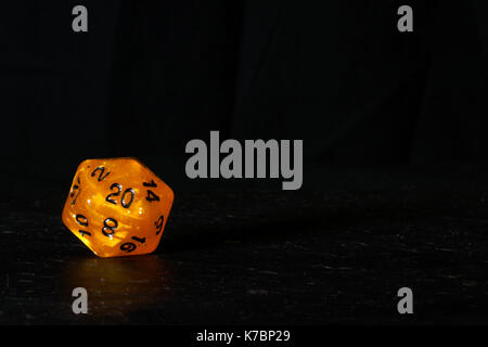 A twenty sided  polyhedral die on a slate surface. These type of dice are used for role playing games such as Dungeons - Stock Photo
