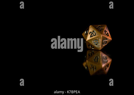 A twenty sided  polyhedral die on a mirrored surface. These type of dice are used for role playing games such as - Stock Photo