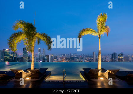 Swimming Pool on roof top and Singapore city skyline in night, Sinagpore - Stock Photo