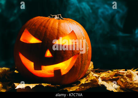 Halloween pumpkin lantern with dry leaves on a smoky dark background - Stock Photo