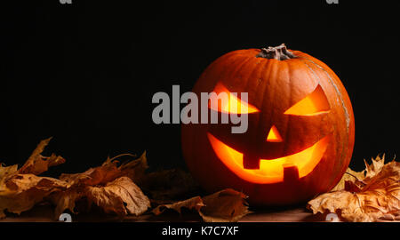 Halloween pumpkin lantern with dry leaves with black background - Stock Photo