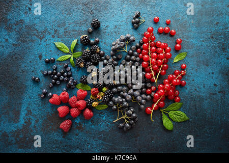 Assorted fresh berries with leaves on metal background. Mix of fresh berries with leaves on textured metal background. - Stock Photo
