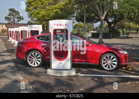 Tesla 'S'  sedan connected to 480 volt Supercharger Station. - Stock Photo