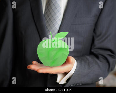 Business man hold a low poly green apple - Stock Photo