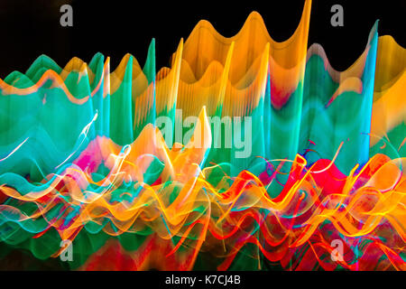 Abstract photo of wavy color lights in motion with a black background.. - Stock Photo