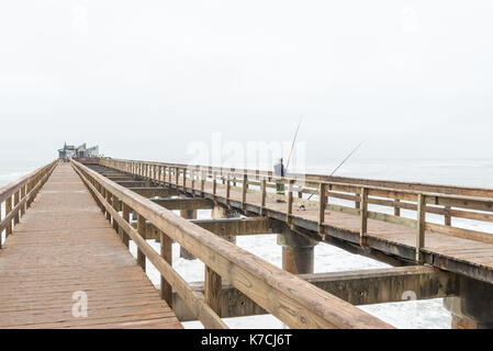 SWAKOPMUND, NAMIBIA - JUNE 30, 2017: An angler on the historic jetty, with a restaurant on its far end, in Swakopmund - Stock Photo