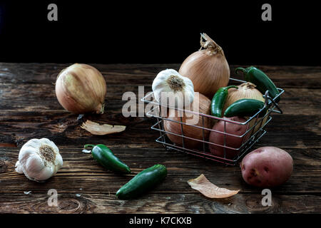 A still life photo of assorted veggies such as garlic, potatoes, peppers, and onions. - Stock Photo