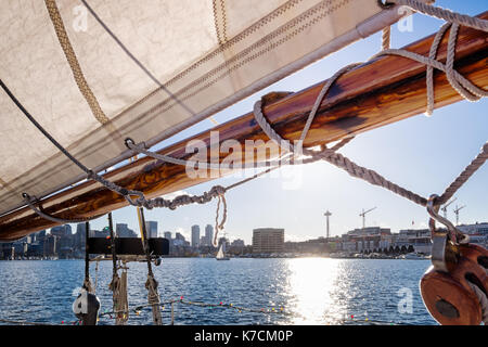 Seattle sailing on Lake Union in a vintage yacht, sailboat. Sail frames a view of the skyline and waterfront, including - Stock Photo