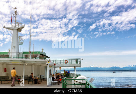SEATTLE-APR 14, 2014: Ferry from Seattle to Bainbridge Island, with the snow capped Cascade Mountains in the background. - Stock Photo