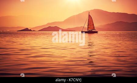Sailboat in beautiful mild orange sunset light, sail race in Mediterranean sea, summer vacation in Turkey - Stock Photo