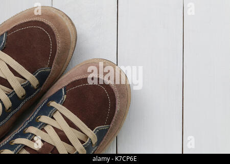 Old sneakers on white wooden floor background and have copy space for design in your work. - Stock Photo