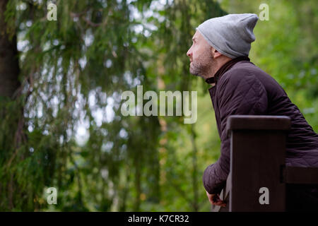 handsome mature man smiling in warm hat and jacket looking aside - Stock Photo