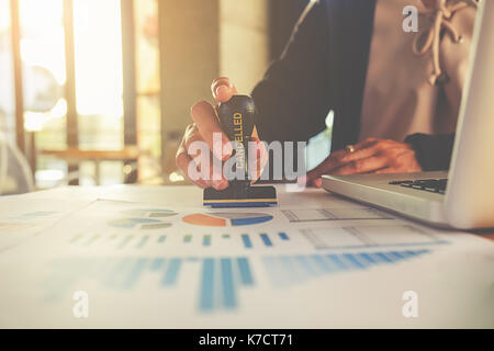 Business concept. Business people Hand Holding Rubber Stamp Over cancelled Stamp On datum. - Stock Photo