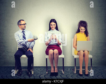 Business man offering money to a young woman using mobile phone sitting next to an employee working on laptop computer - Stock Photo